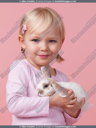 Portrait of a three year old smiling girl holding a pet rabbit in her hands isolated on pink background