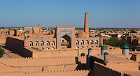High angle view of Muhammad Rakhim-khan II Madrasah, 1871, seen  from a terrace of Ichan Kala, Khiva, Uzbekistan, pictured on July 5, 2010, in the afternoon. Just inside the Kun Ark Citadel, the Muhammad Rakhim-khan II Madrasah is one of the biggest Madrasahs in Khiva. Commissioned by Muhammad-Rahim II (1863-1910), it has a two tiered celled facade, with a massive central portal, and small towers at the corners. Khiva, ancient and remote, is the most intact Silk Road city. Ichan Kala, its old town, was the first site in Uzbekistan to become a World Heritage Site(1991). Picture by Manuel Cohen.