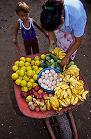 small mexican boy with a whellbarrow ful of fruits and eggs for sale. Buyer inspecting the goods