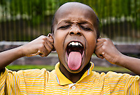 A young African-American boy making a face: scrunching up his eyes, sticking out his tongue and pulling his ears.