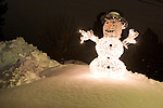 An illuminated snowman sits a top a pile of fresh snow at night.