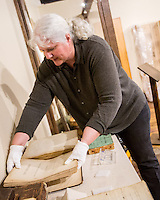 NWA Democrat-Gazette/JASON IVESTER --03/31/2015--<br /> Marie Demeroukas, photo archivist, places a pair of mid-1800's Bibles back into a display case on Tuesday, March 31, 2015, inside the Shiloh Museum of Ozark History in Springdale.