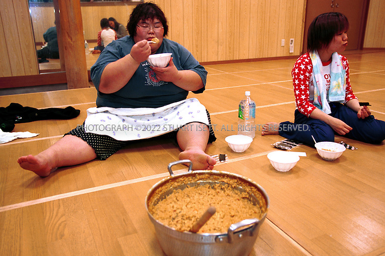 10/25/2001--Osaka, Japan..Rie Tsuihiji, 23, Japan's leading female sumo wrestler and 2000 world champion, enjoys curry risotto after a training session at her company's sumo club..Photograph by Stuart Isett/Gamma.©2002 Stuart Isett All rights reserved