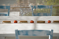 A row of wooden scrubbing brushes and tomatoes makes an unusual centre-piece on the dining table on the covered terrace