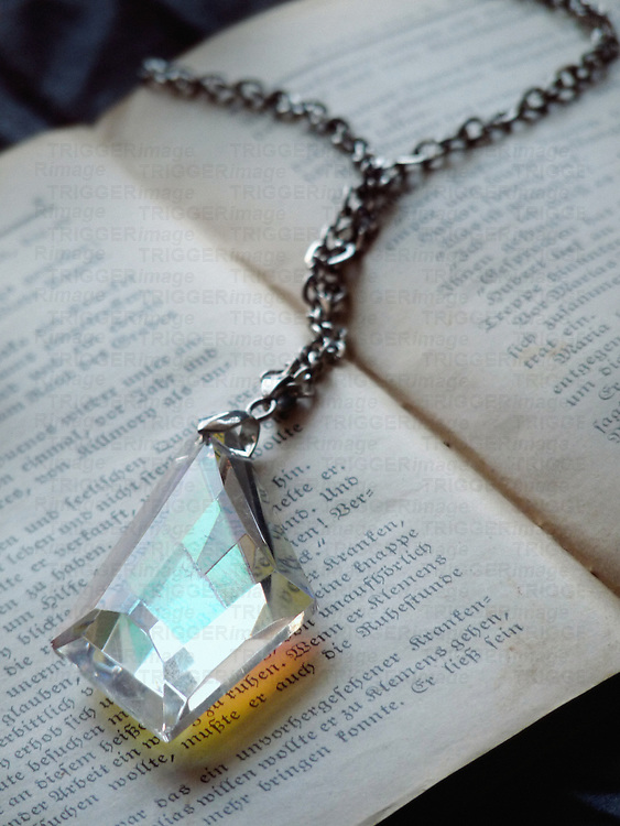 A vintage crystal pendant with a silver chain, laying on an old book.