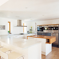 The contemporary kitchen is a combination of white units and work surfaces, wood and stainless steel