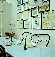 Behind the enamelled lava-stone table and cafe-style bentwood bench in the kitchen an entire wall is taken up by a collection of framed prints and drawings