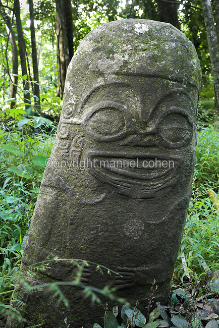 Smiling Tiki, stone carved male tiki sculpture with smiling face, 93cm tall, wearing a bonnet, with facial features and tattoos in relief and hands on the belly, at the meae or religious sanctuary of Utukua, on the island of Hiva Oa, in the Marquesas Islands, French Polynesia. Tiki sculptures represent Ti'i, a half-human half-god ancestor who is believed to be the first man. Tiki often have a huge head, symbolising power, and big eyes symbolising knowledge. Tiki are respected and are often placed outside houses as protective statues. Picture by Manuel Cohen