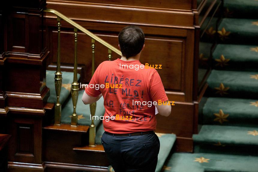 """Laurent Louis, le député du MLD était présent ce jeudi 26 avril à la Chambre des Parlementaires de Bruxelles. Il portait un t-shirt  où il arborait un slogan """" Libérez le MLD, la vérité pour le peuple """". Visé par des perquisitions mercredi dans le cadre d'une instruction pour des faits de calomnie, diffamation et recel, Laurent Louis a demandé jeudi à la Chambre de suspendre les poursuites à son encontre suite à des documents papiers et informatiques qui ont été saisis lors de quatre perquisitions menées mercredi à Nivelles au domicile du député fédéral Laurent Louis ainsi qu'à son bureau à la Chambre,. Laurent Louis (Independent) pictured with a t-shirt 'Liberez le MLD, La vérité pour le peuple' (Free MLD (aka his party)."""