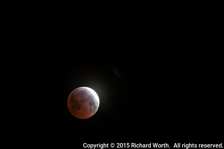 A lunar eclipse, in progress, nearing maximum on April 5, 2015.  Viewed from near San Francisco, California.