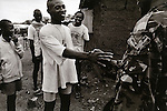 Lester, 19, meets a former soldier friend from his old unit..Freetown,Sierra Leone, May 1997