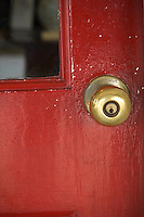 Close up of brass door knob on bright red door.