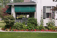 Summer garden next to house and front porch with hollyhocks, impatiens