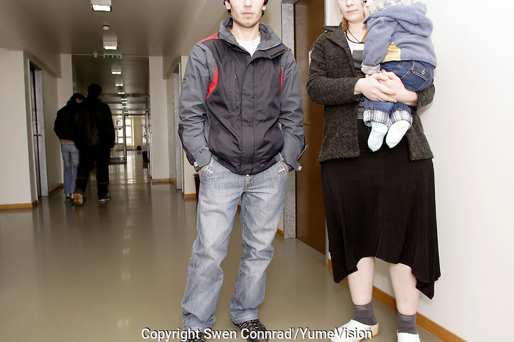 A Chechen refugee family in the corridor of the room floor, at the Vallorbe registration Centre of the Swiss Federal Office for Refugees (CERA)..There lifes was in permanent threat in Chechnya..They reaches Switzerland 2 week ago hide in the back of a lorry. .The newly born boy is under medical treatment for having be oblige by the human smugglers, to take over dose of sedative during the hided and silenced journey to reaches Switzerland..They are now on procedure of registration, hoping to be accepted. .The CERA of Vallorbe have a capacity of 200 bed and cover. A inside and outside kindergarten, a library within different religious book but a shortage of Koran, a daily visiting cleric, a inside open courtyard for football, 2 dining room who are also Tv and gaming room, 3 copious and equilibrate meal per day are offer to the refugees, an 20 Securitas (private security company) working on 24h a day shift. .High wire netting with barbed wire on the top and video surveillance are all over the building, but all the door of the building are 24h open to exit say the head Securitas.