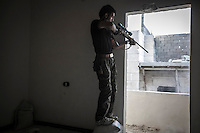 ABU AHEMD, the sniper of the Kateba Omar Ben Abdul Aziz targets the army troops from a house building as he fights at the Aamria battlefield embedded inside a civilian neighborhood at the southwest of Aleppo City.