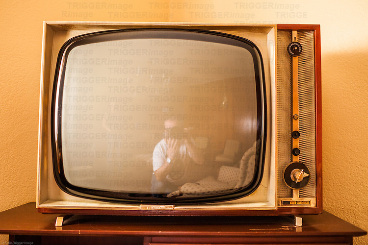 Vintage TV in an old fashioned hotel room, Guadalara, Spain with reflection of photographer