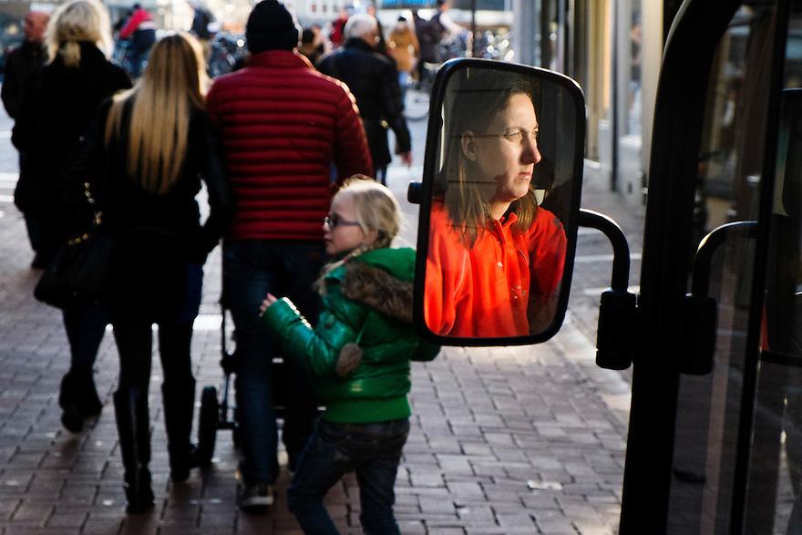 Nederland, Amsterdam, 3 febr 2014<br /> Schoonmaakwagentje rijdt door winkelstraat. De chauffeuse is in de spiegel van het wagentje te zien<br /> Foto: Michiel Wijnbergh