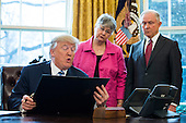 U.S. President Donald J. Trump reads on of three executive actions that he said are 'designed to restore safety in America' while Attorney General Jeff Sessions (R) and his wife, Mary Blackshear Sessions (C) look on in the Oval Office of the White House in Washington, DC, USA, 09 February 2017. On 08 February, after a contentious battle on party lines, the Senate voted to confirm Sessions as attorney general.<br /> Credit: Jim LoScalzo / Pool via CNP