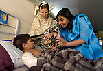 In the Sheikh Zayad Hospital in Lahore, Pakistan, Sanober Nathaniel (right), a student at the historically church-related Kinnaird College for Women, visits with a young earthquake victim and her mother. Nathaniel is applying henna to the girl's hand in celebration of Eid el-Fitr, the celebration of the end of the Muslim holy month of Ramadan. Students at Kinnaird collected money and clothing for earthquake victims that was distributed through Church World Service and the Church of Pakistan, both members of Action by Churches Together, the global alliance of churches and church-related agencies responding to emergencies..