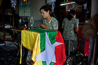 A woman makes a new Burmese flag in a workshop in Yangon. The Burmese government introduced the new flag in the lead up to the elections scheduled for 07/11/2010.