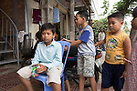 Bunroeun with some of his close friends..A Khmer boy learns to play classical violin at the college of Beaux Arts, at the edge of Cambodia's capital, Phnom Penh. He is an orphan and comes from a poor family. His parents died long ago, from AIDS related diseases. He lives with his grandmother and his uncle, and their family. He lives on the top floor of an apartment block, where his family run a textile business, sewing together clothes and ornamental flags from around the world. A dozen young women work in this textile business, and the boy's home space is actually amidst this small factory environment which he shares with them. They eat, work and play together like an extended family or community. Phnom Penh, Cambodia