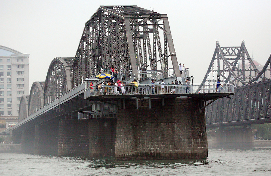 """A view of a bridge that once linked North Korea to China in over the Yalu River July 9, 2006. The bride was bombed """"accidentally"""" by Americans during the Korean war and has now been converted in to a war memorial.  DPRK, north korea, china, dandong, border, liaoning, democratic, people's, rebiblic, of, korea, nuclear, test, rice, japan, arms, race, weapons, stalinist, communist, kin jong il"""