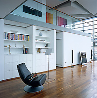 A violin has been placed on a leather chair next to a music stand in the open-plan living area of this contemporary apartment