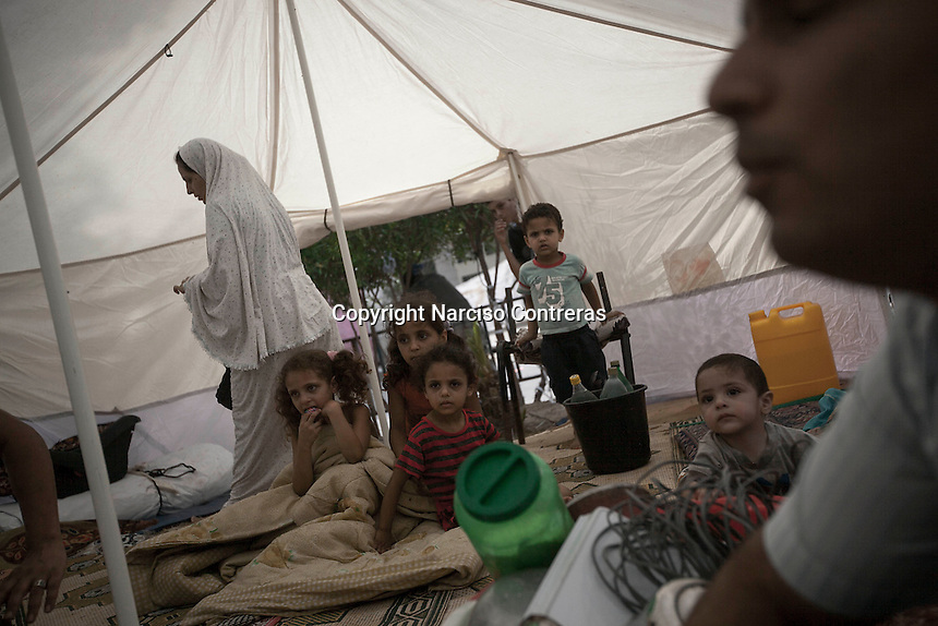 "In this Friday, Aug. 15, 2014 photo, the family of Ashaf Abu Kuamar (not pictured) sit inside a tent in a temporary shelter set up around Al-Shifa hospital as their home remains in ruins after it was completely destroyed during the ""Protective Edge"" Israeli military operation in Shuyaja neighborhood in Gaza City. After a five days truce was declared on 13th August between Hamas and Israel, civilian population went back to what remains from their houses and goods in Gaza Strip. (Photo/Narciso Contreras)"
