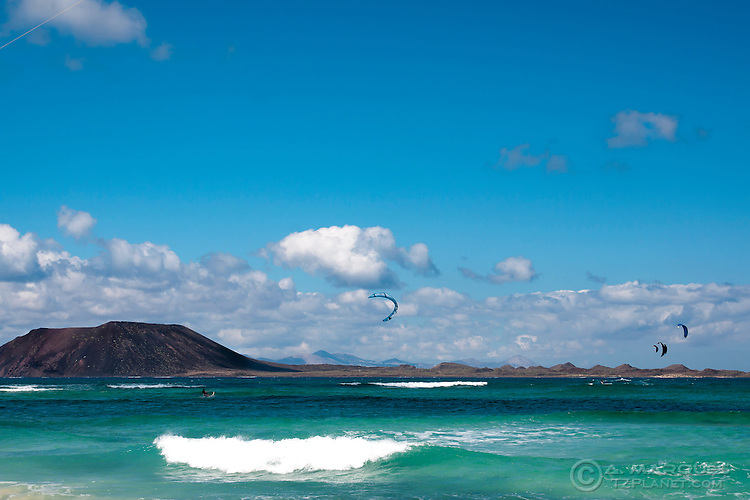 Kitesurfers in Fuerteventura with Los Lobos in background. Kitesurfing / kiteboarding is a very popular water sport in Fuerteventura, Canary Islands, Spain. The east coast, with sandy beaches and strong winds, is a popular destination for water sports like windsurfing and kiteboarding. Dozens of kitebraders can sometimes be seen in the water. Many water sports schools cater for the beginners, the large majority of which are tourists.