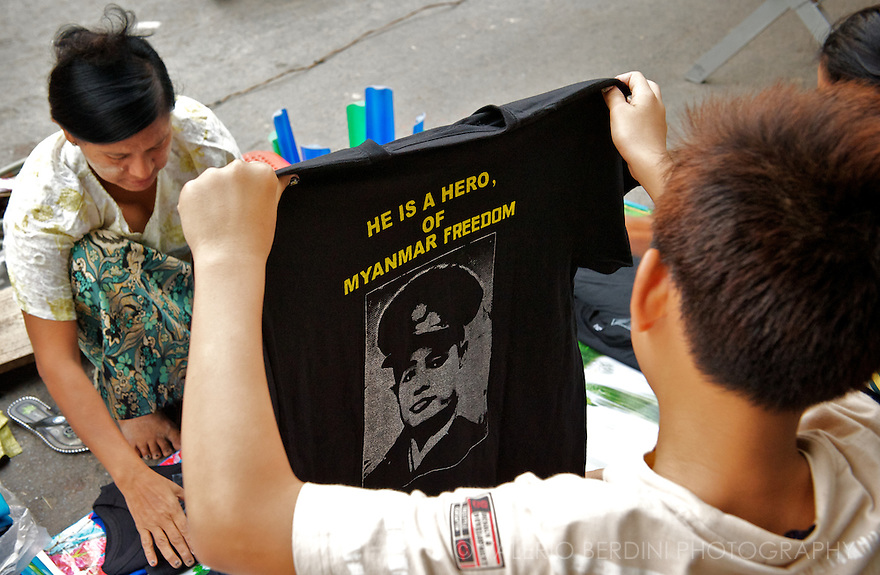 A teenager reads a T-Shirt with the image of General Aung San, esteemed as a hero and a martyr of Myanmar struggle for Indipendence..Mandalay, Myanmar. 2012