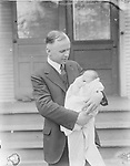MATCHING HAIRLINES. This father looks appropriately enthralled, while his baby yawns.<br /> <br /> Photographs taken on black and white glass negatives by African American photographer(s) John Johnson and Earl McWilliams from 1910 to 1925 in Lincoln, Nebraska. Douglas Keister has 280 5x7 glass negatives taken by these photographers. Larger scans available on request.