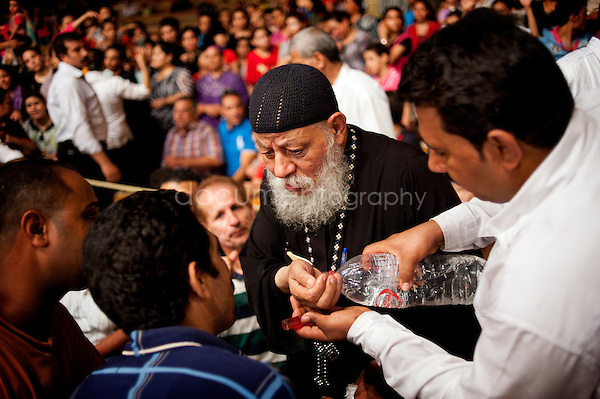 Followed by one of his devoted carrying bottles filled with holy water, Father Samaan uses it to throw in the faces of men and women coming to receive from him exorcism session.<br />