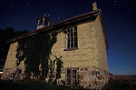 Abandoned One-Room Rural Canadian School House Lit by Full Moon with Star Trails in the Sky
