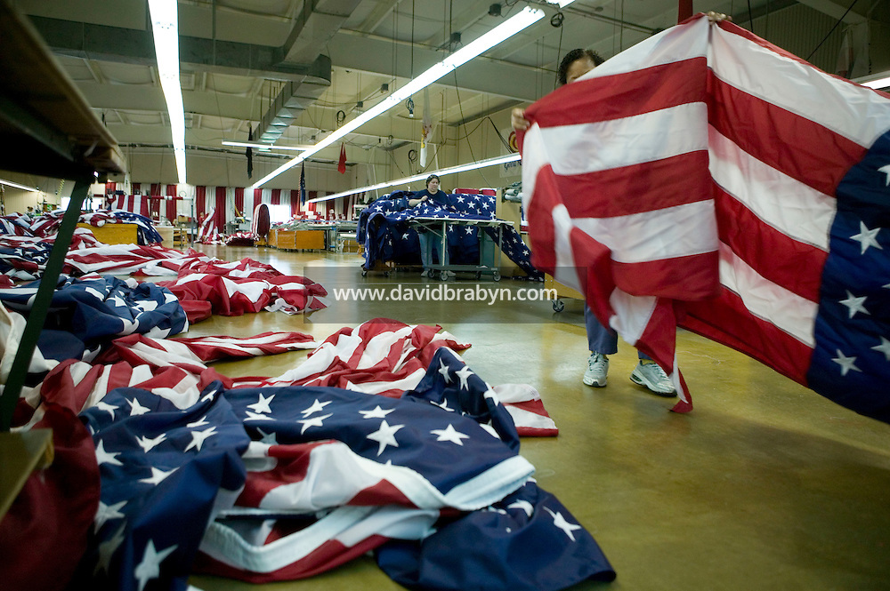 21 June 2005 - Oaks, PA - Estrellita Harris (hidden) and Nancy Rotay (not pictured) fold a completed American flag at the Annin & Co. flag manufacturing plant in Oaks, PA. Photo Credit: David Brabyn.