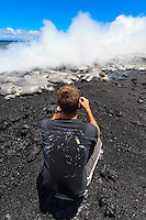A man takes a photo of lava meeting the ocean at Fox's Landing black sand beach on the Big Island.
