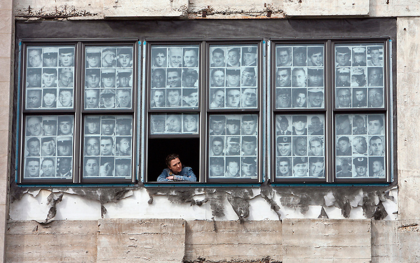 SIDEWALKS. Carrie Iverson stands in the window of her memorial to soldiers killed in Iraq at Chicago Printmakers, 4642 N. Western, Tuesday, April 3 , 2007. The photos of fallen soldiers have been on view in the Printmakers' windows since the summer of 2004, on the same level as the passing el train. Chicago Tribune Photo by Charles Osgood  ..OUTSIDE TRIBUNE CO.- NO MAGS,  NO SALES, NO INTERNET, NO TV, CHICAGO OUT.. 00276690A sidewalks