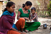 Pramila Tharu (center), 15, has lunch with her 2 year old toddler Prapti in her fields in Bhaishahi village, Bardia, Western Nepal, on 29th June 2012. Pramila eloped and married at 12 and gave birth to Prapti at age 13. She delivered prematurely on the way to the hospital in an ox cart and her baby weighed only 1.5kg at birth. In Bardia, StC works with the district health office to build the capacity of female community health workers who are on the frontline of health service provision like ante-natal and post-natal care, especially in rural areas. Photo by Suzanne Lee for Save The Children UK