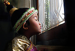 A girl wearing traditional cloathes waits for the start of a  Lao wedding in Luang Prabang.