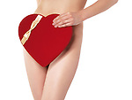 Sexy young woman covering her body with a red heart-shaped Valentine's Day gift box. Isolated on white background.