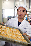 Zenya Oikawa, managing director of Oizen Shoten, loads freshly baked sasa-kamaboko onto shelves for cooling at the company's factory in Tome City, Miyagi Prefecture, Japan on 11 Sept. 2012.  Photographer: Robert Gilhooly