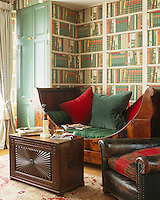 A mahogany Empire day bed with large green and red velvet cushions in a guest room in which the walls have been papered to resemble shelves of books
