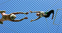 "Cassy Caldwell, 12, jumps towards ""catcher"" Kevin Six (L) while on the trapeze. This is shot through the net that catches them if they miss their jump.  (Photo by Fred Greaves)"