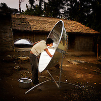 A youth cleaning a solar cooker at a Bhutanese refugee settlement. The cooker has to be cleaned after every meal in order to keep the surface working as effectively as possible. With the financial help of the Dutch Council for Refugees, a total of 6,300 solar cookers will be distributed amongst the Bhutanese refugees living in the region. The solar cookers consist of a reflective, aluminium, parabolic-shaped device that concentrates the sun's rays onto cooking pots placed on a frame in the centre of the dish. The dish has to be adjusted to the new position of the sun around every 10 minutes. It takes about 55 minutes to prepare a cooked meal on a sunny day and it is hoped that using the solar cookers will alleviate pressure on resources and reduce kerosene consumption by 75%...