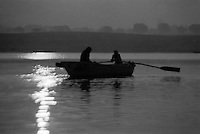 India, Uttar Pradesh, Varanasi, 1999. Two brothers row on the Ganges in the magic light of early morning. In winter, the great, wide river is at its slowest and most peaceful.