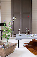 The living room is a symphony of muted greys and white and an antique armoire creates an interesting contrast