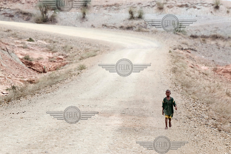 A child walks beside an unpaved road in the dry landscape at the border of Amhara and Tigray region. Ethiopia is experiencing its worst drought in over 50 years. The emergency started early in 2015 with the failure of the February-April 'Belg' rains and was further compounded by the main 'Kiremt' rain season (July-September) being erratic and poor, caused by an exceptional El Nino event.