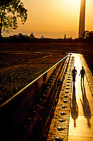 Two men walking next to the Vietnam Veterans Memorial at sunrise, Washington D.C., USA
