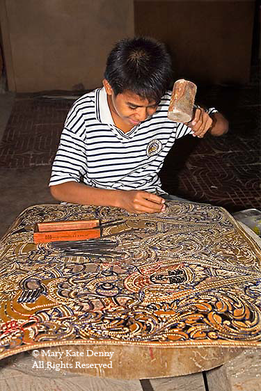 Siem Reap, Cambodia_Cambodian young boy hammers nail into leather to carve ...