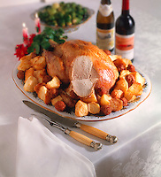 Whole roast turkey on a platter with roast potatoes with soft wine & vegetables behind