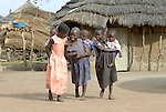 Girls carrying younger siblings walk through a camp for internally displaced persons in northern Uganda. Almost two million people were displaced by the two-decade conflict, which began winding down with peace talks in 2006. By 2007, a few displaced families had returned home.